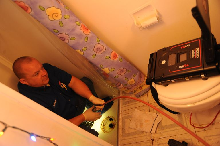 Plumber in bathroom monitors remote inspection camera